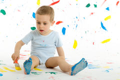 Adorable 3 year old boy child creatively stains on the wall. Adorable 3 year old boy child creatively stains on the wall, floor with colourful paint. Mess of Stock Photography