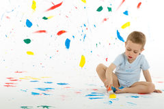 Adorable 3 year old boy child creatively stains on the wall. Adorable 3 year old boy child creatively stains on the wall, floor with colourful paint. Mess of Royalty Free Stock Photography