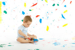 Adorable 3 year old boy child creatively stains on the wall. Royalty Free Stock Images