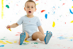 Adorable 3 year old boy child creatively stains on the wall. Adorable 3 year old boy child creatively stains on the wall, floor with colourful paint. Mess of Stock Photos