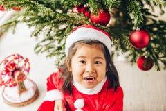 Adorable 3 year old toddler girl enjoying Christmas time. Christmas portrait of adorable 3 year old asian toddler girl wearing red Santa dress and hat, sitting stock images