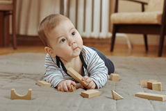 Adorable young baby boy playing with his toys Stock Photos