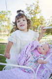 Adorable Young Baby Girl Playing with Baby Doll and Carriage royalty free stock photo