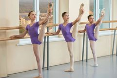 Adorable young ballerinas stretching legs. Three beautiful young ballerinas raised legs at ballet barre in dance class. Ballet performers having practice stock photography