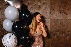 Adorable young blond with long hair wearing sparkly dress posing at camera with ballons and have fun, birthday party, happy stock images