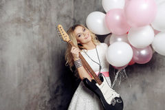 Adorable Young Blonde With Guitar At The Party. Holding A Large Bundle Of Balloons. On Gray Textured Background. Stock Image