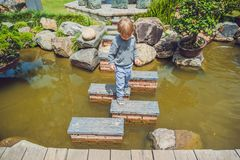 Adorable young boy with crossing river or water jumping from rock to rock. Crossing the gap, freedom, liberation, success, avoidin Royalty Free Stock Photography