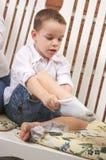 Adorable Young Boy Getting Socks On Stock Image