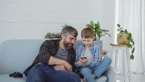 Adorable young boy and his caring father are using smartphone, talking and laughing together pointing at screen. Modern. Adorable young boy and his caring father stock footage