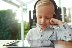 Adorable young boy listening to music. Adorable young boy sitting with a tablet computer listening to his music library with a happy smile of contentment on a Royalty Free Stock Photos