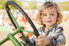 Adorable Young Boy Playing on an Old Tractor Outside Royalty Free Stock Images
