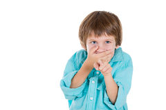Adorable young boy, pointing with one hand, closing mouth with other and laughing at you Royalty Free Stock Image