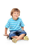 Adorable young boy sitting on a skateboard. Isolated against white background Royalty Free Stock Photography