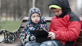 Adorable young boy watching his brother. As the two sit together on a wooden park bench in warm winter clothing with the older child using a tablet computer stock video