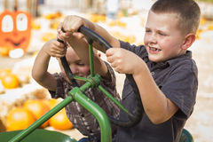 Adorable Young Boys Playing on an Old Tractor Outside royalty free stock photography