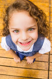 Adorable young brunette girl standing on wooden Royalty Free Stock Photography