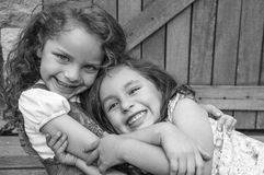Adorable young brunette girls embracing hugging Royalty Free Stock Photography