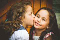 Adorable young brunette girls kissing on cheek. Showing love and friendship Stock Photography