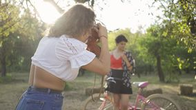 Adorable young caucasian woman with short hair posing with her bicycle while her friend taking a photo in the garden or. Attractive young caucasian woman with stock footage