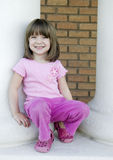Adorable young child. Wearing pink pants and top standing by school columns stock images