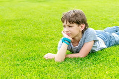 Adorable young child boy in the park. Adorable young child boy laying on the grass in the park. On warm summer day during school holidays. Kid boy dreaming and stock image