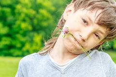 Adorable young child boy in the park. On warm summer day during school holidays. Kid boy dreaming and smiling royalty free stock images