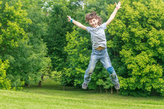 Adorable young child boy in the park. On warm summer day during school holidays. Kid boy jumping and smiling stock images