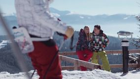 Adorable young couple standing on the observation deck high in the mountains and talking to each other, while skiers. Pass by. Sunny winter day. Romantic stock footage
