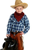Adorable young cowboy hands on hip holding saddle Stock Photos