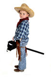 Adorable young cowboy riding a stick horse werious Royalty Free Stock Photo