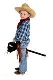 Adorable young cowboy riding a stick horse werious. An adorable young cowboy riding a stick horse Royalty Free Stock Photo