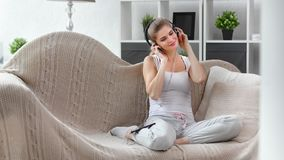 Adorable young female relaxing at sofa listening music wearing headphones using smartphone. Full shot. Domestic European beautiful smiling girl enjoying weekend stock footage