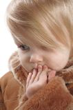 Adorable young girl. Portrait of adorable little girl in winter coat with hand up to her mouth Royalty Free Stock Photo