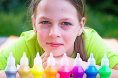 Adorable young girl with colorful bottles of paint in front of h Royalty Free Stock Photography