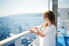 Adorable young girl enjoying ferry ride staring at the deep blue sea. Child having fun on summer family vacation in Greece stock image