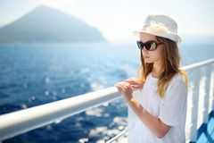 Adorable young girl enjoying ferry ride staring at the deep blue sea. Child having fun on summer family vacation in Greece royalty free stock photography