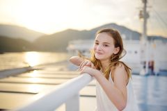 Adorable young girl enjoying ferry ride staring at the sea on sunset. Child having fun on summer family vacation in Greece stock photo