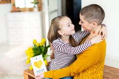 Adorable young girl giving her mom, young cancer patient, homemade I LOVE MOM greeting card. Happy Mother`s Day or Birthday. stock photos
