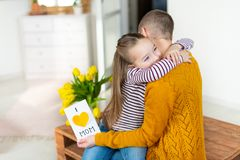 Adorable young girl giving her mom, young cancer patient, homemade I LOVE MOM greeting card. Family concept. Happy Mother`s Day. stock images