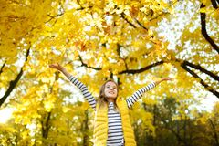 Adorable young girl having fun on beautiful autumn day. Happy child playing in autumn park. Kid gathering yellow fall foliage royalty free stock image