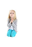 Adorable young girl kneeling in prayer looking up Stock Photo