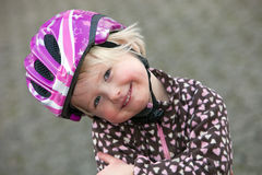 Adorable young girl in a pink safety helmet Stock Images