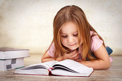 Adorable young girl reading a book Stock Images