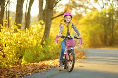 Adorable young girl riding a bike in a city park on sunny autumn day. Active family leisure with kids. Child wearing safety helmet while riding a bicycle stock photo
