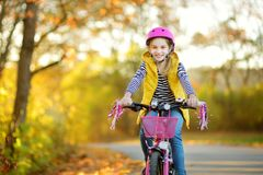 Adorable young girl riding a bike in a city park on sunny autumn day. Active family leisure with kids. Child wearing safety helmet while riding a bicycle royalty free stock photo