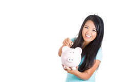 Adorable young girl saving her earnings in her piggybank Stock Photo