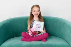 Adorable young girl sitting on a couch, holding bouquet of pink gerbera daisies and Mother`s day card. Happy Mother`s Day. Adorable young girl sitting on a Stock Photo