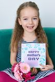 Adorable young girl sitting on a couch, holding bouquet of pink gerberas and Mother`s day card. Happy Mother`s Day. Concept Royalty Free Stock Photos