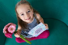 Adorable young girl sitting on a couch, looking up and holding bouquet of pink gerbera daisies and Mother`s day card. POV, mother`s personal perspective angle Royalty Free Stock Photos