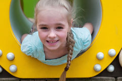 Adorable young girl sitting in crawl tube Stock Photo